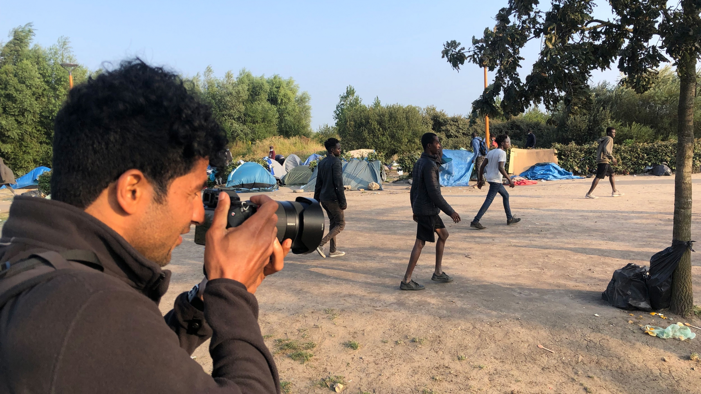Abdul Saboor, an award-winning Afghan photographer in France, documents a soccer game at a refugee encampment in Calaís, France.