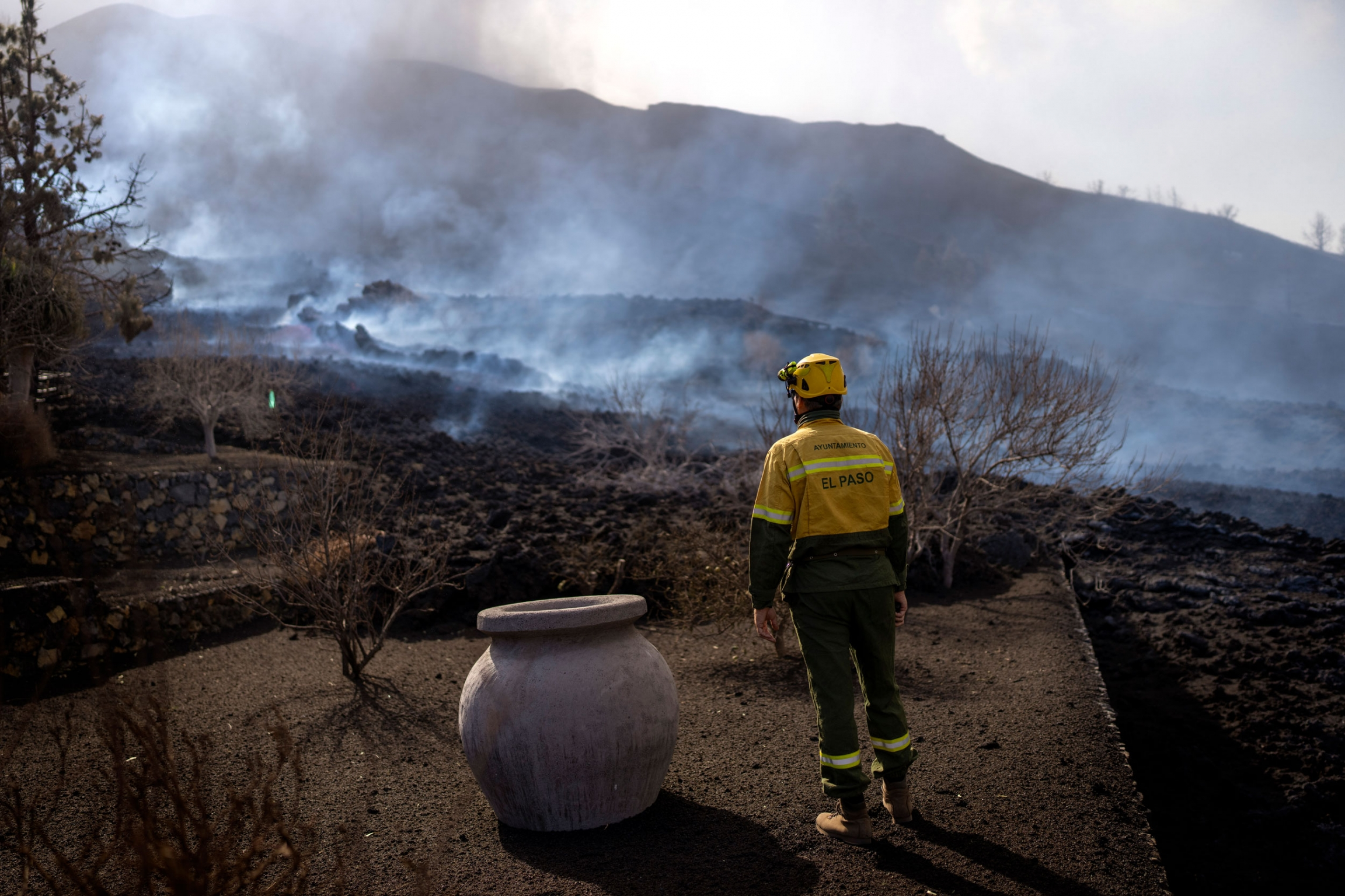A municipal worker looks as smoke rises after a volcano erupted, near El Paso on the island of La Palma in the Canaries, Spain, Tuesday, Sept. 21, 2021.