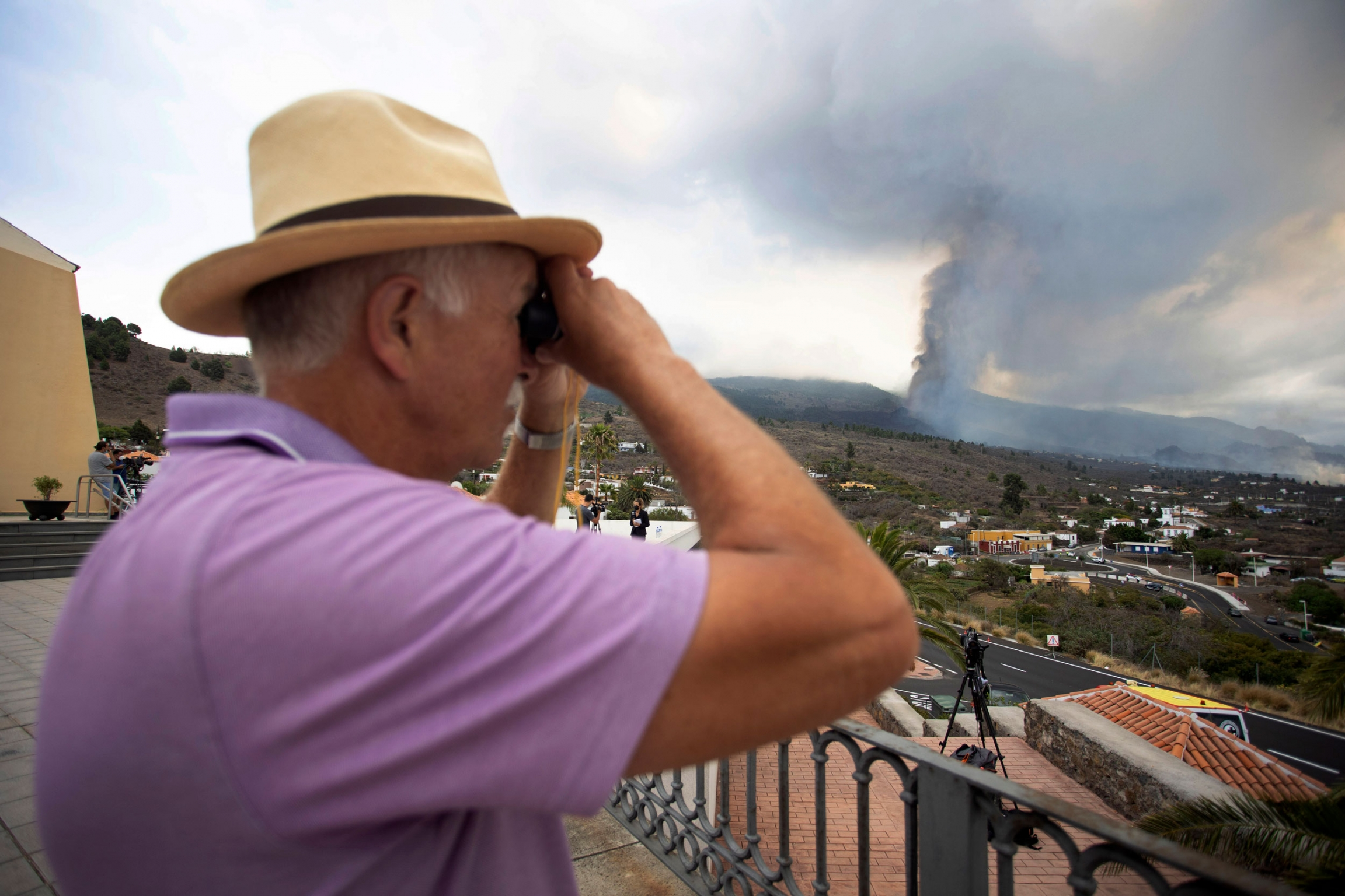 A man looks out towards the eruption of a volcano near El Paso on the island of La Palma in the Canaries, Spain, Monday, Sept. 20, 2021.