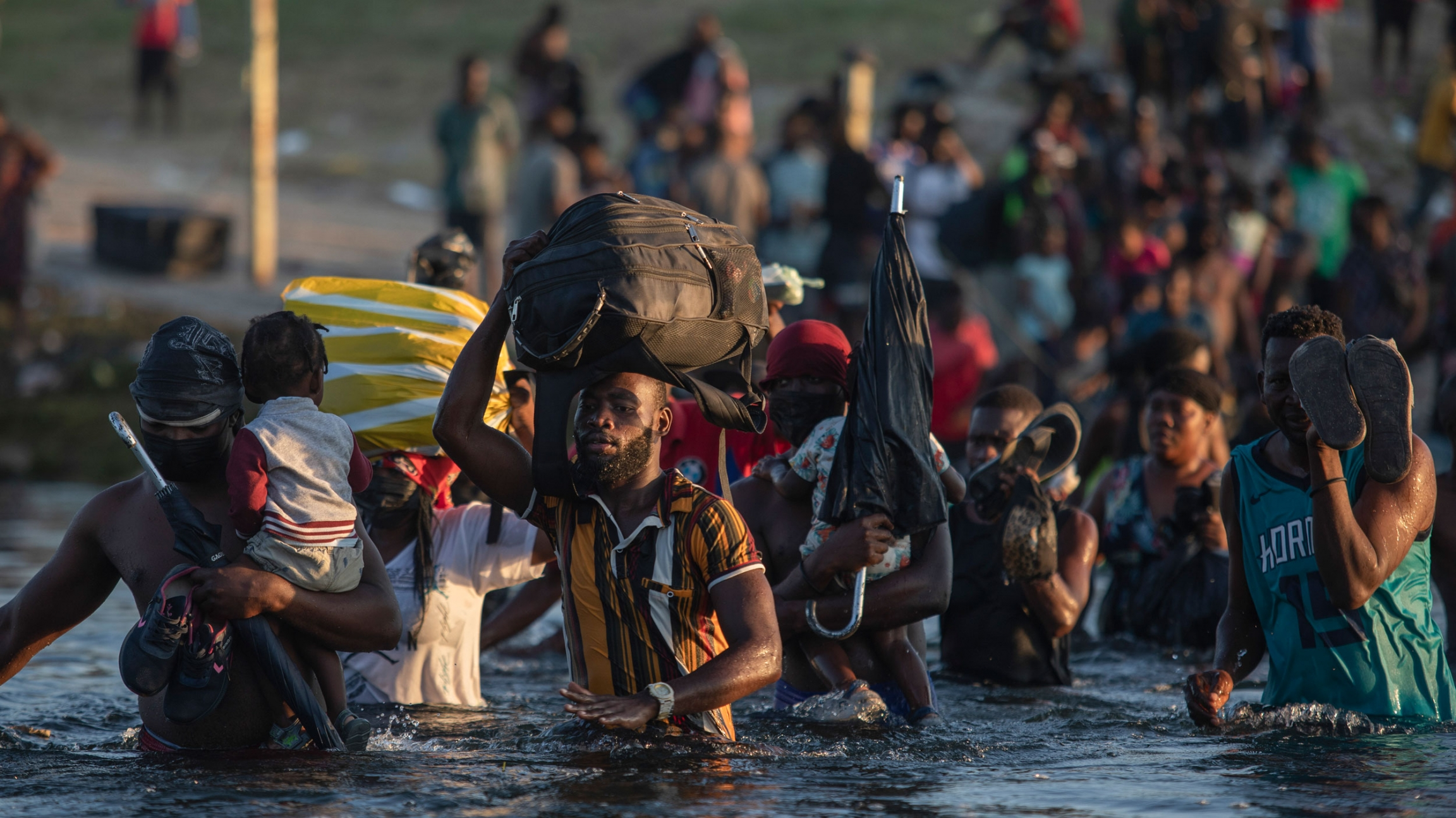 Migrants, many from Haiti, wade across the Rio Grande river from Del Rio, Texas, to return to Ciudad Acuña, Mexico, Monday, Sept. 20, 2021, to avoid deportation from the US.