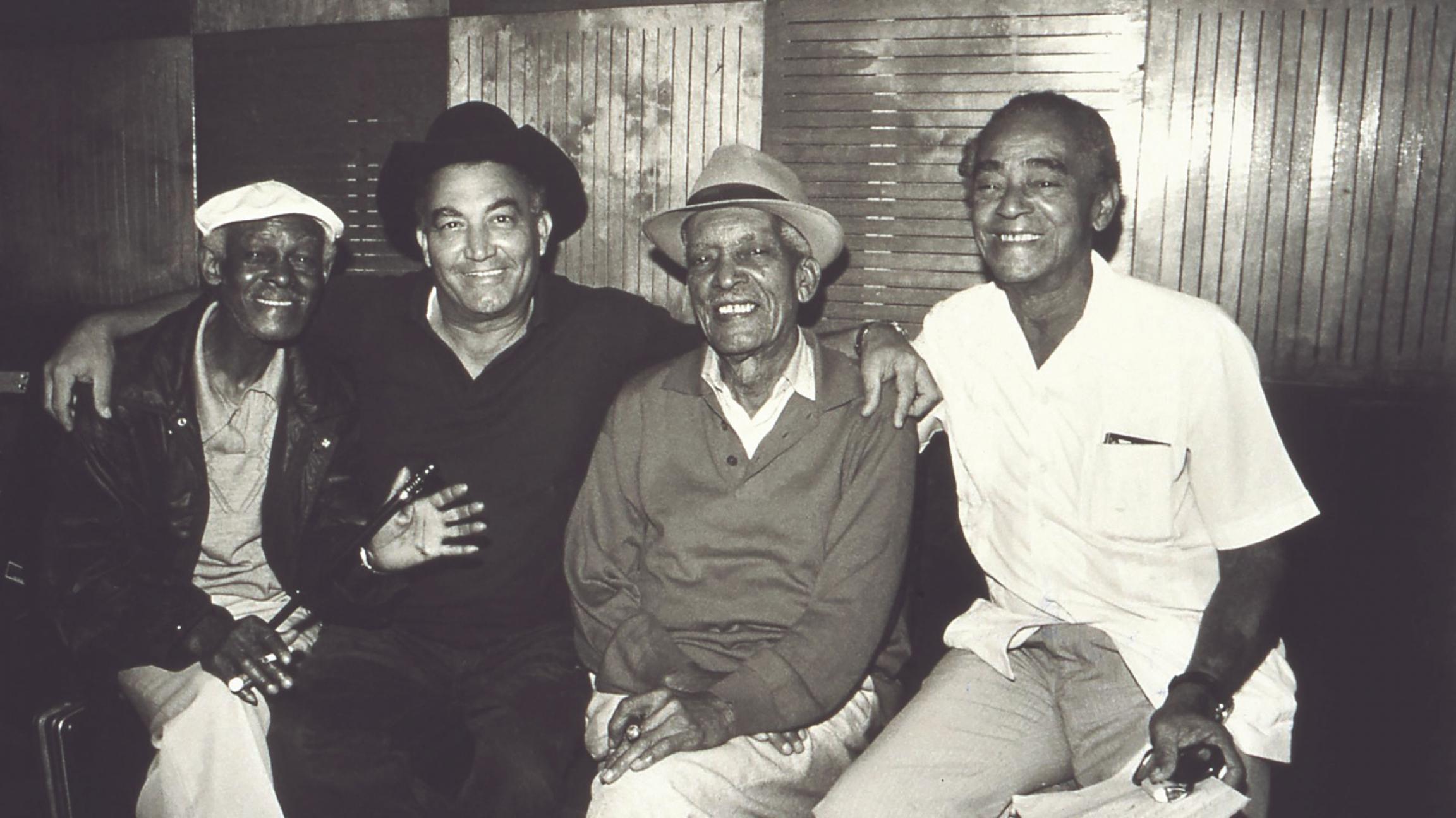 A black and white photo of Buena Vista Social Club members Ibrahim Ferrer, Eliades Ochoa, Comapy Segundo and Puntillita Licea.