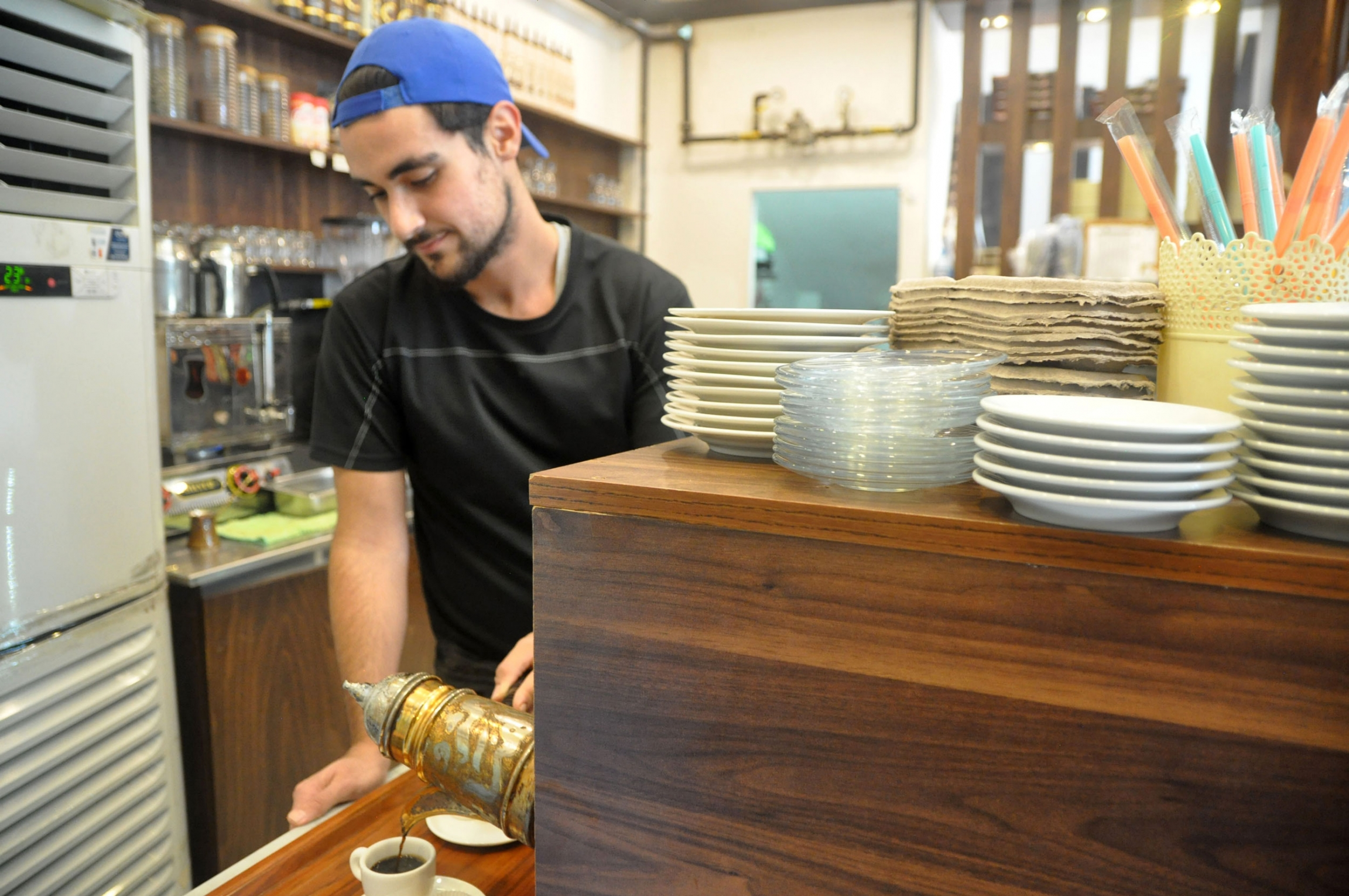 A worker pours a cup of strong coffee at a Syrian sweet shop in Istanbul. Unemployment rates in Turkey are high, and the pandemic affected Syrian workers particularly severely.