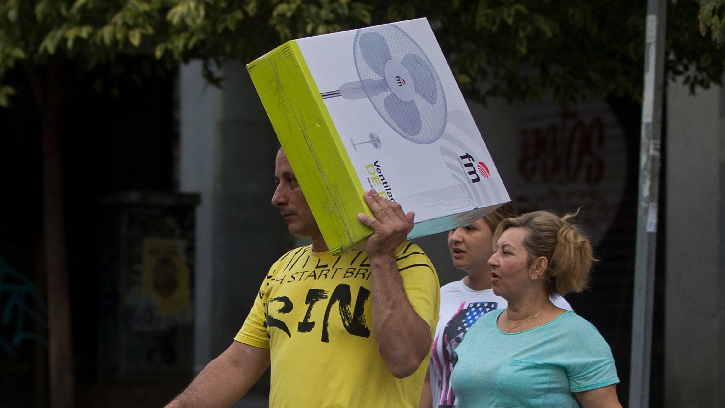 In this June 15, 2017 file photo, a man carries a boxed electric fan in Madrid, Spain. Spanish consumers are fretting over record-high power prices.
