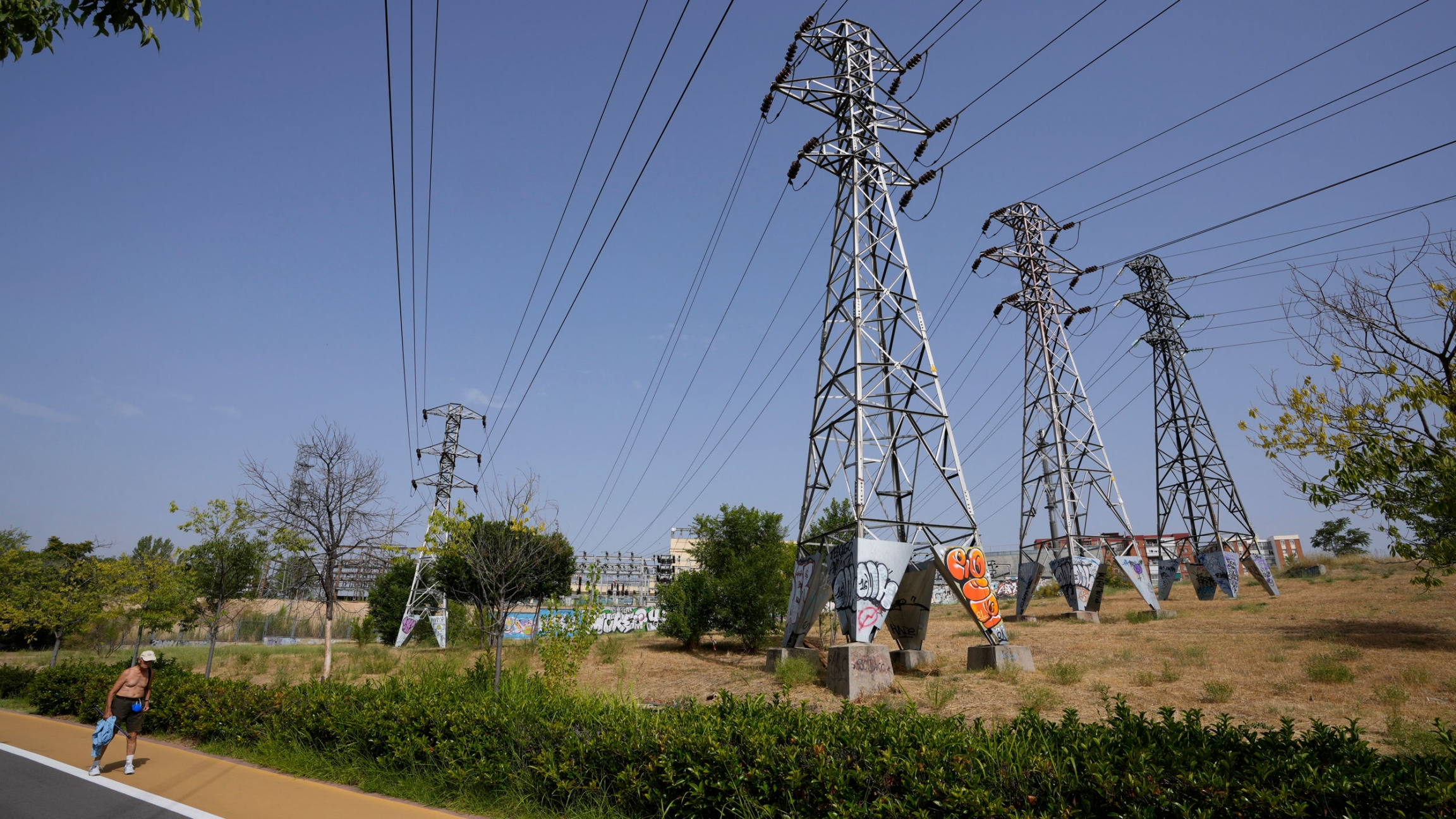 A man walks past electricity pylons at an electricity sub station in Madrid, Spain, Wednesday, Aug. 11, 2021.