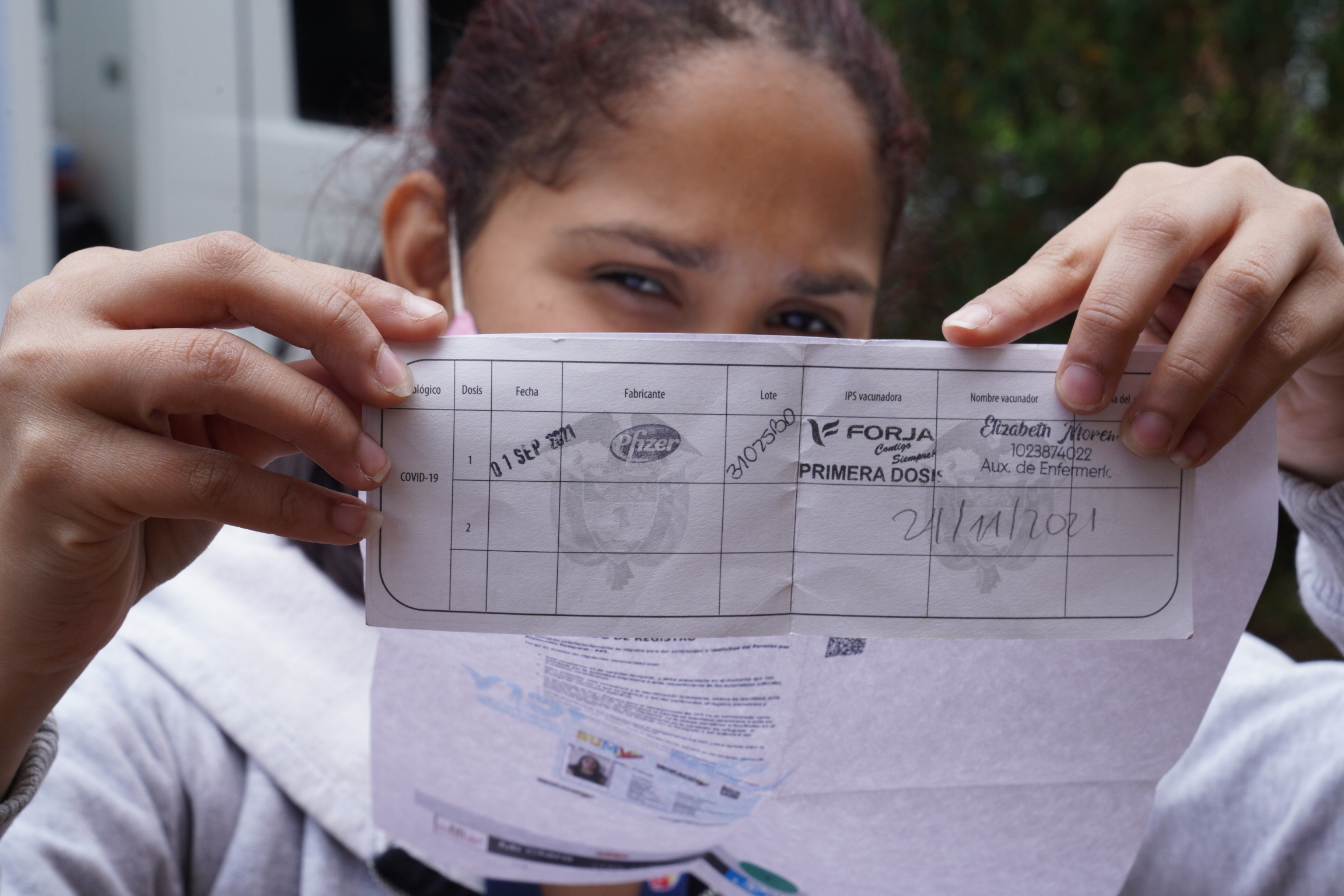 Oriana Fernandez Fernandez got her first dose of the Pfizer Vaccine in Bogota during the first week of September. But only after completing her TPS application and showing a sheet with a QR code that proved it.