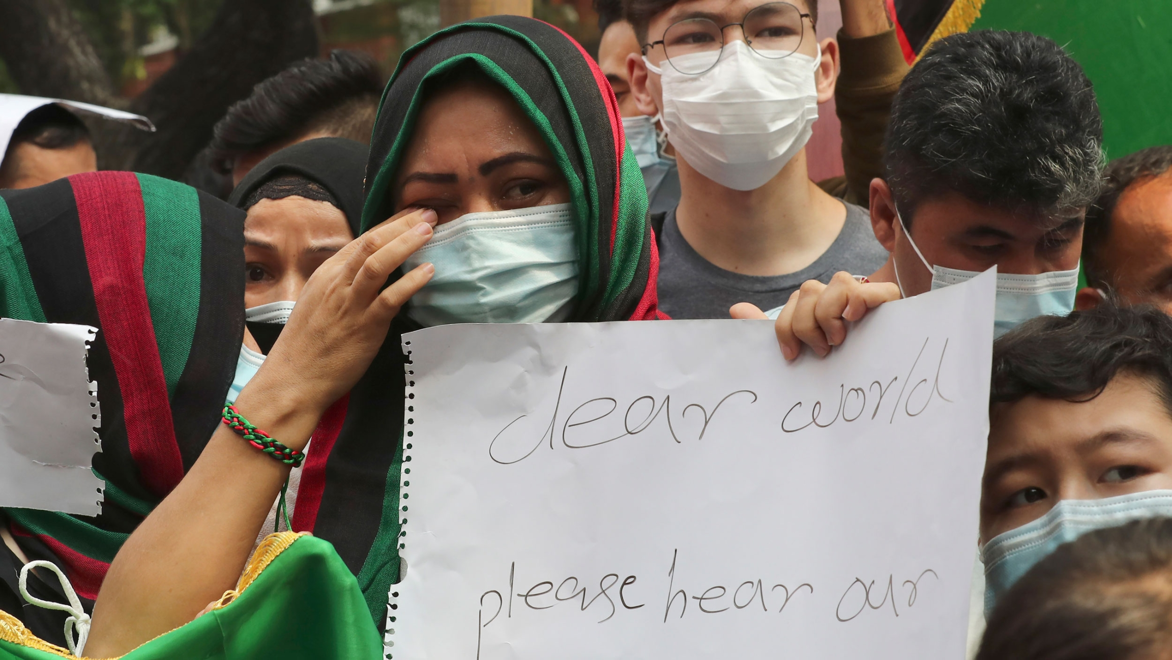 An Afghan woman weeps as she holds a poster during a rally outside the building that houses UNHCR representative office in Jakarta, Indonesia, Tuesday, Aug. 24, 2021.