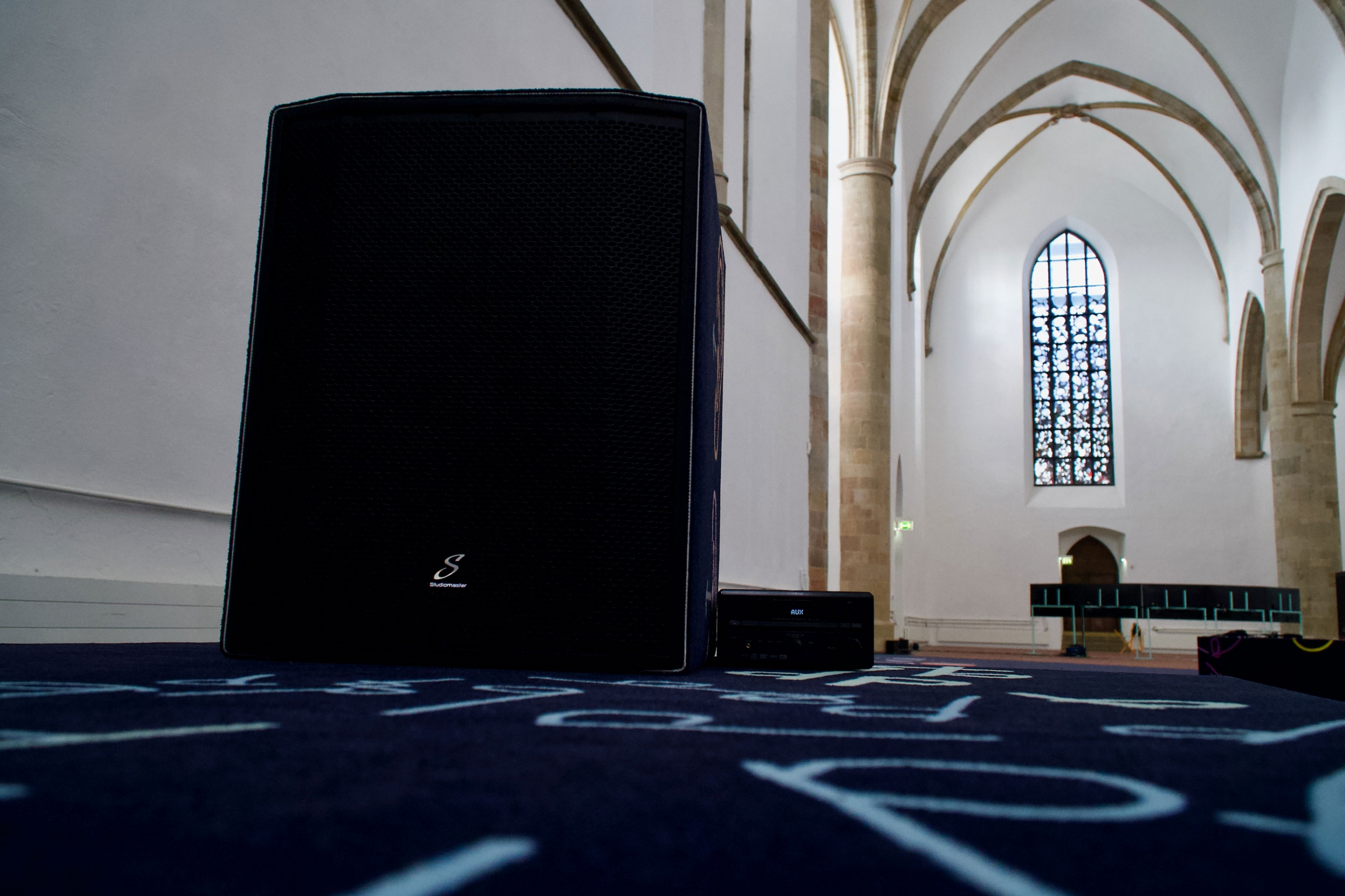 An up-close image of a speaker within a church with high ceilings.