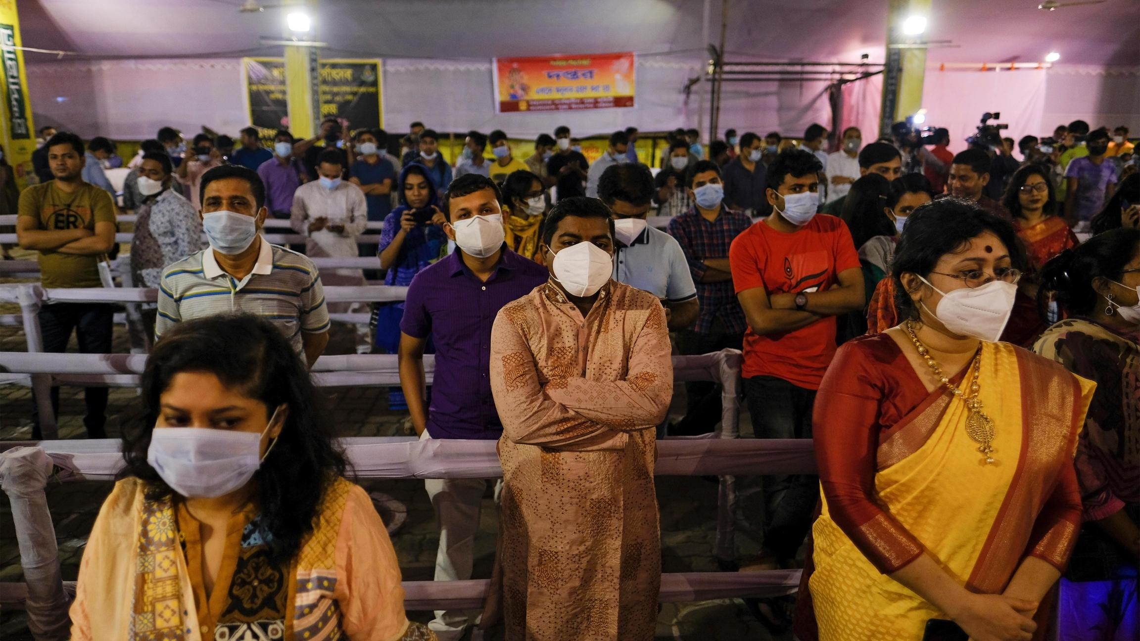 People wearing masks as a precautionary measure against the coronavirus assemble to offer prayers at Dhakeshwari Temple during a Hindu Durga Puja festival in Dhaka, Bangladesh