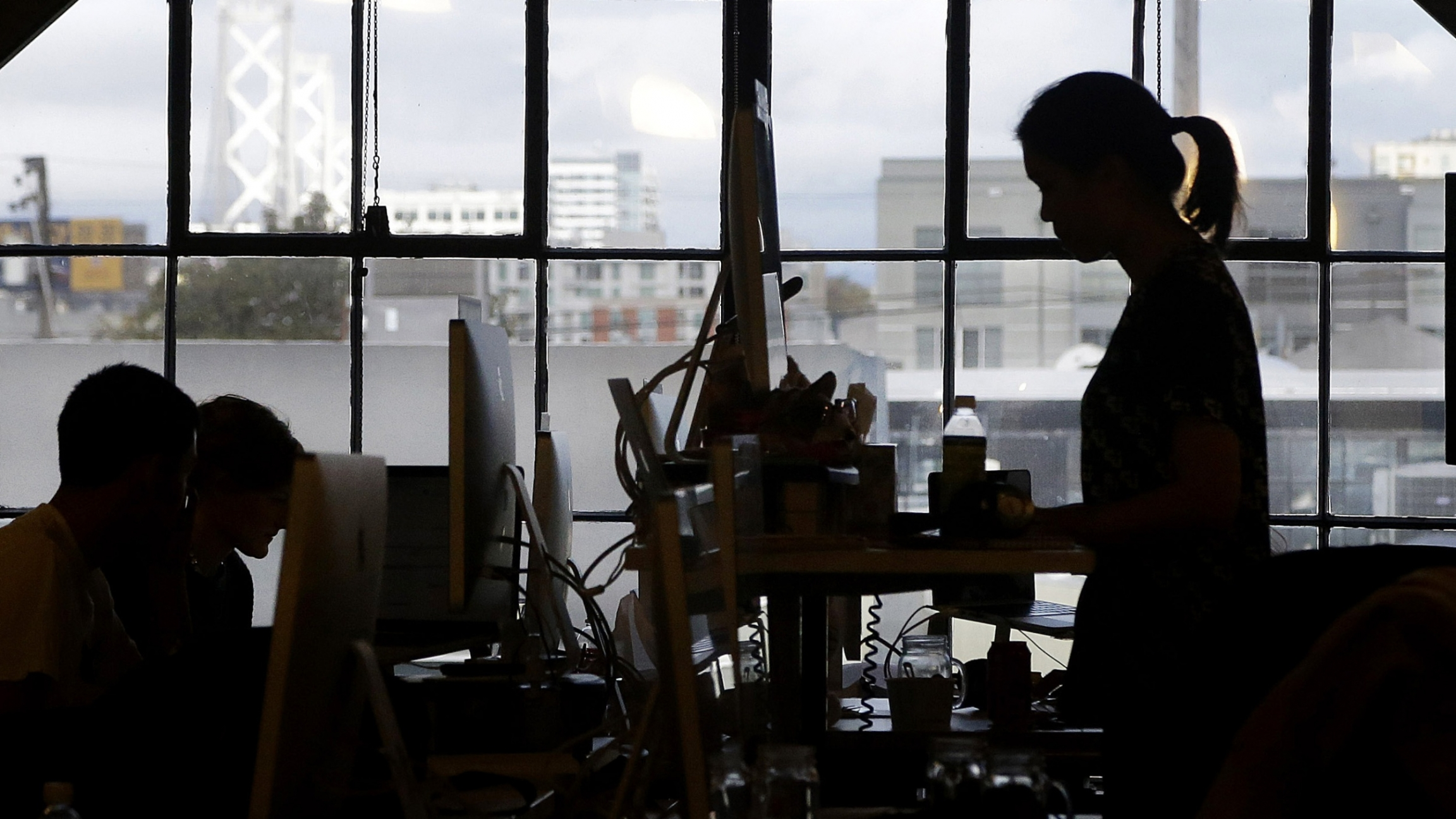 Office worker silhouetted in front of a window