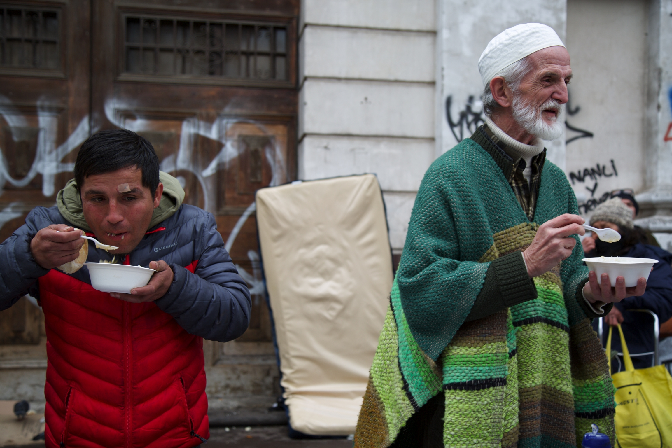Chilean Muslims and people from other religious communities eatinga meal from bowls, outsideat the weekly soup kitchen in Santiago, Chile.