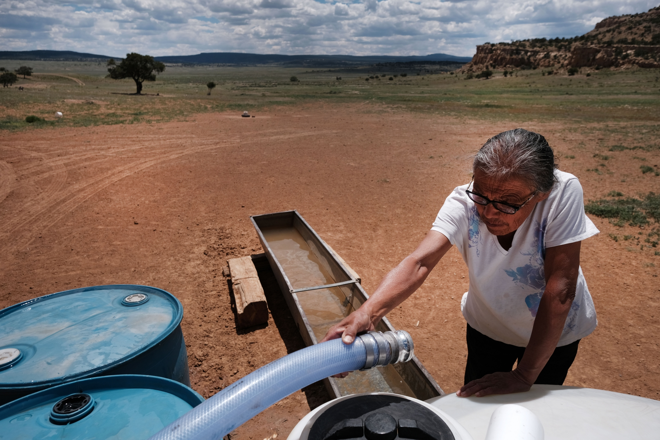 Woman holding hose from truck to fill water trough