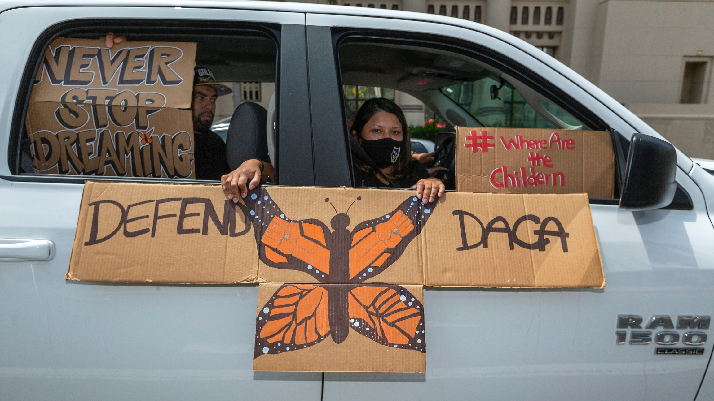 An immigrant family joins members of Coalition for Humane Immigrant Rights of Los Angeles, CHIRLA, on a vehicle caravan rally to support the Deferred Action for Childhood Arrivals Program (DACA), around MacArthur Park in Los Angeles,June 18, 2020.