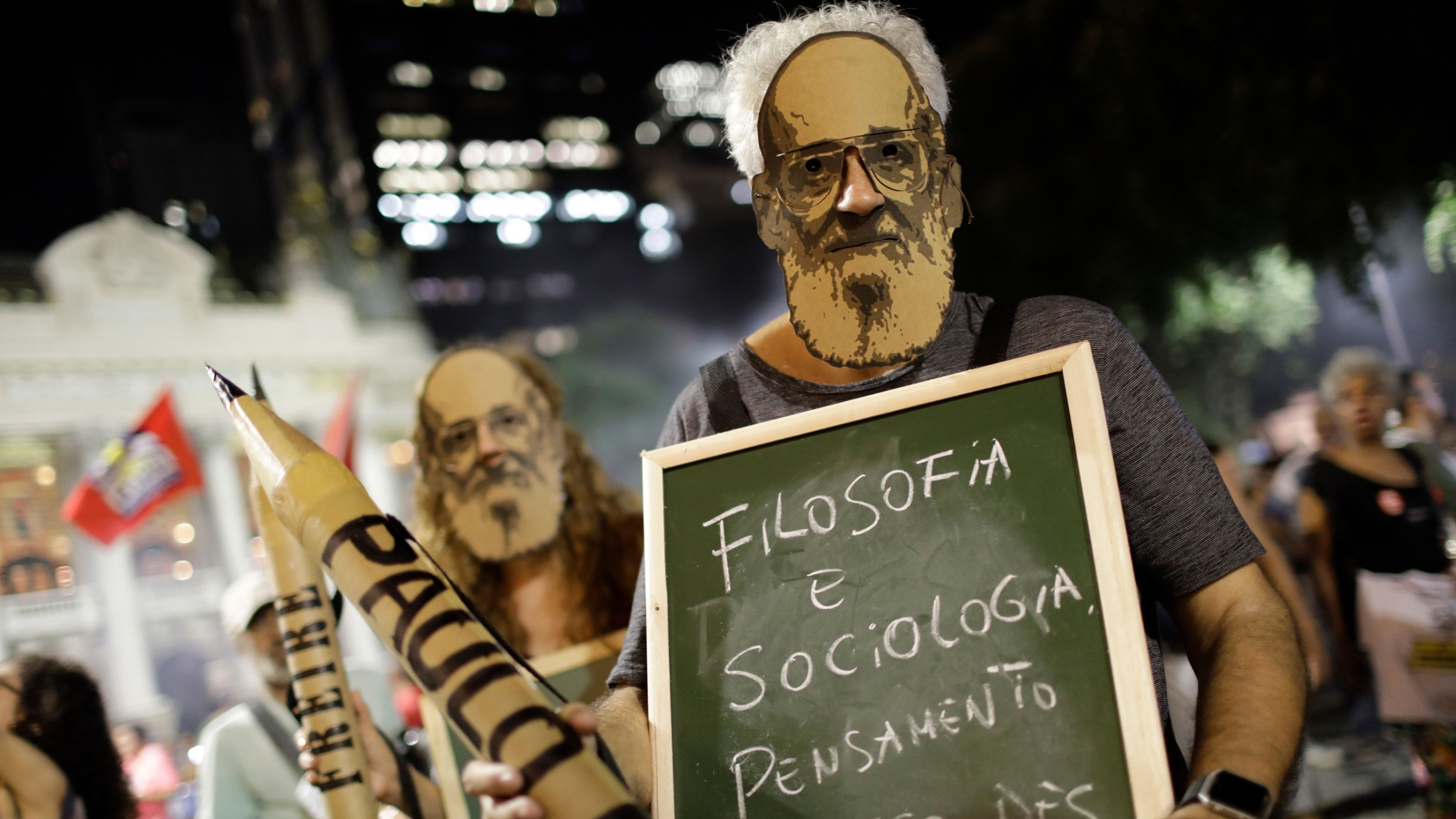 People wear masks of Paulo Freire during a protest against a massive cut in the education budget imposed by the administration of Brazilian President Jair Bolsonaro at Cinelandia square, in Rio de Janeiro, Brazil, Thursday, May 30, 2019.