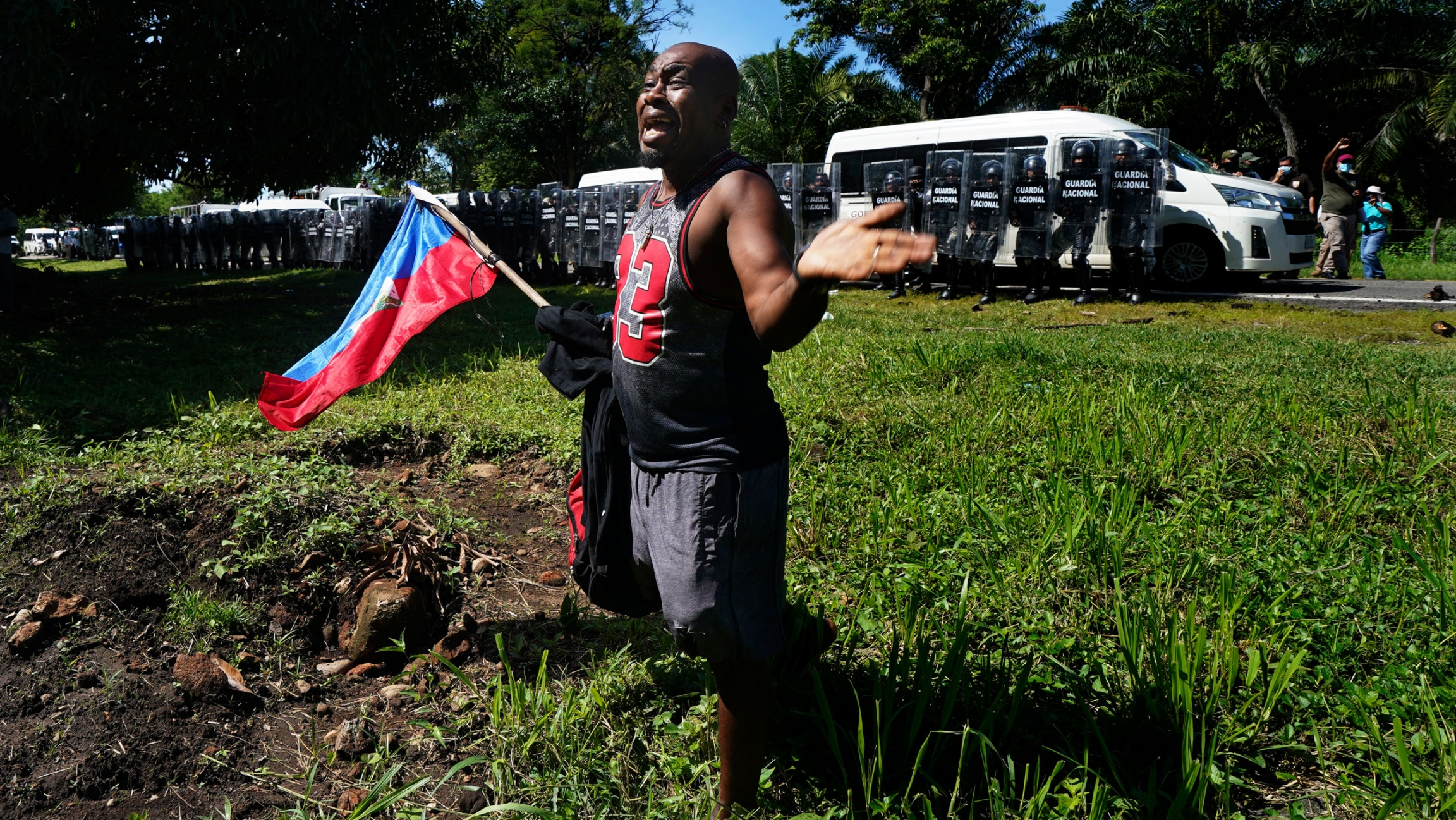 A Haitian migrant, holding his country's national flag, pleads with Mexican National guardsmen not to detain migrants making their way to the US-Mexico border, in Escuintla, Chiapas state, Mexico, Thursday, Sept. 2, 2021.