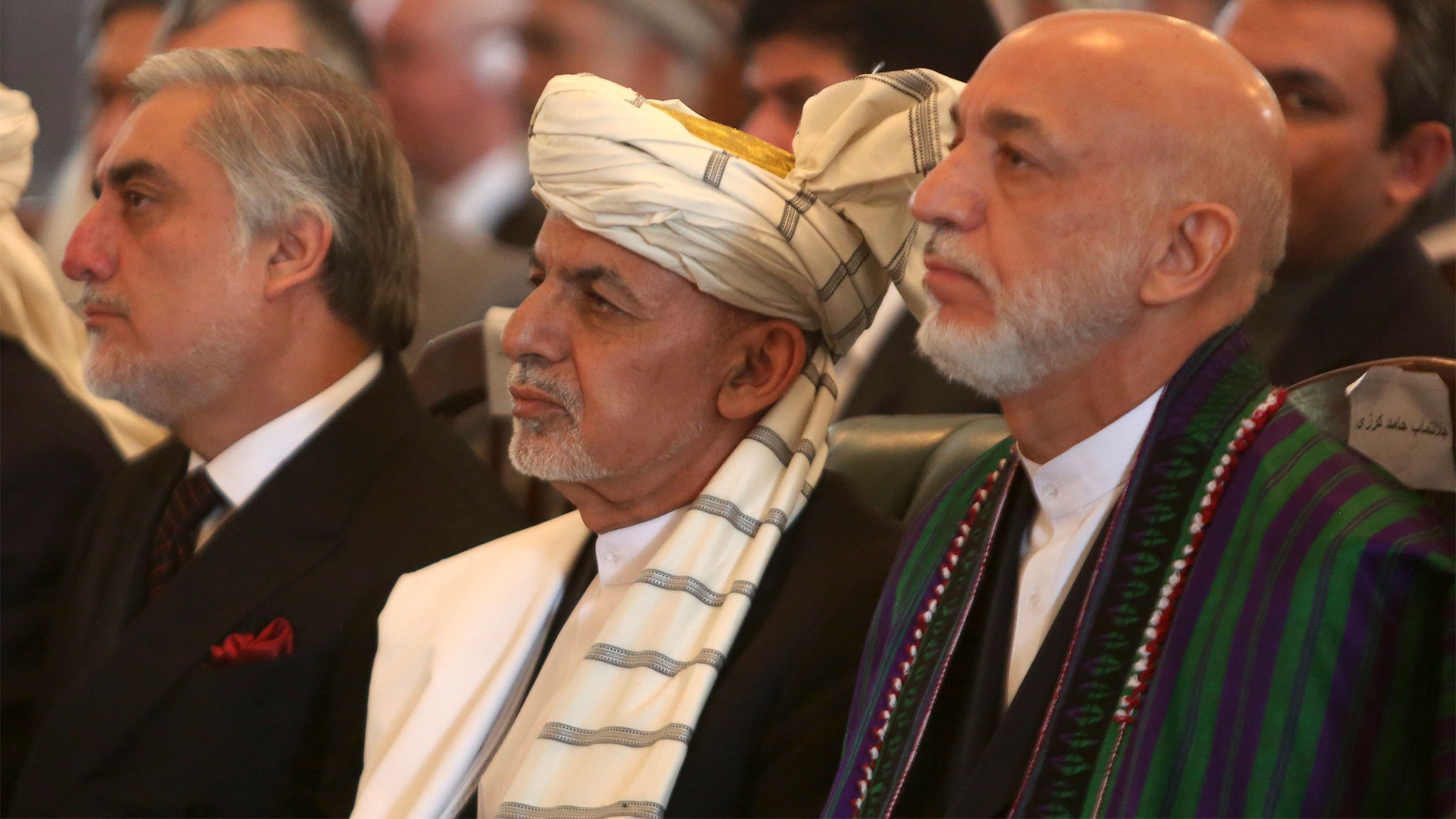 Afghan President Ashraf Ghani, center, former President Hamid Karzai, right, and Chief Executive Abdullah Abdullah, left, watch the live broadcast of Gulbuddin Hekmatyar after the signing of a peace treaty at the presidential palace in Kabul, Afghanistan