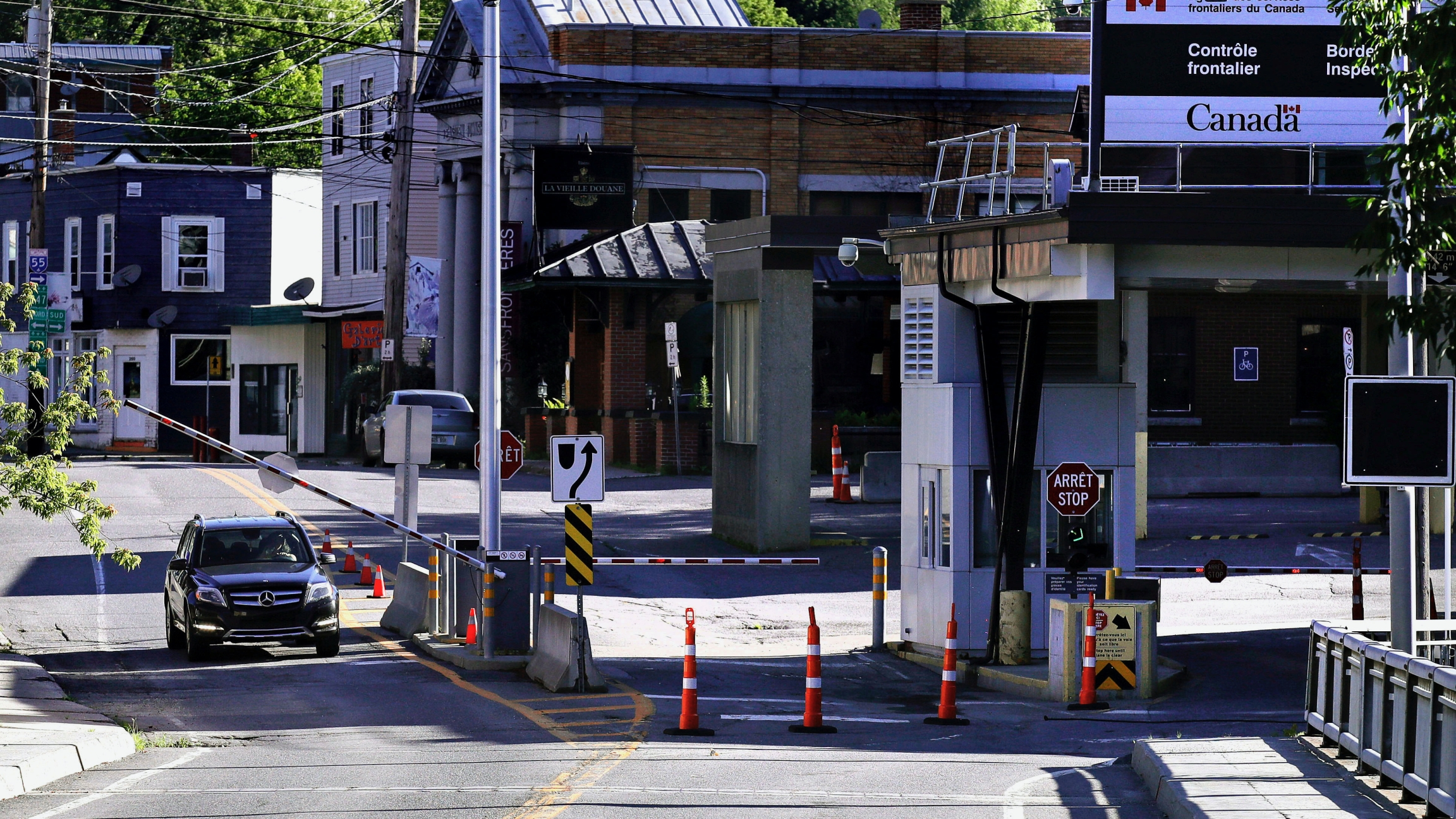 A vehicle in Canada waits for a gate to rise while crossing into Derby Line, Vt. from Stanstead, Quebec, July 11, 2018.
