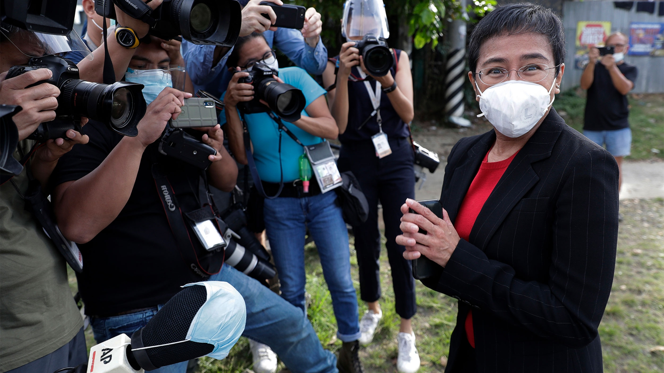 Rappler CEO and Executive Editor Maria Ressa, right, stands in front of reporters as she arrives at the Court of Tax Appeals in Metro Manila, Philippines