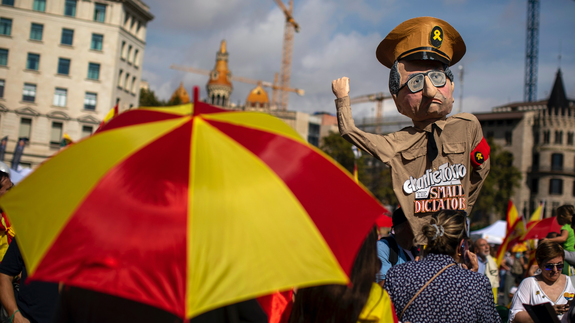 """A demonstrator holds a paper doll representing regional Catalan President Quim Torra, as they celebrate a holiday known as """"Dia de la Hispanidad"""" or Spain's National Day in Barcelona, Spain,Oct. 12, 2019. Spain commemorates Christopher Columbus' arrival"""