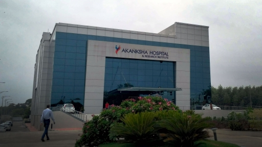 A large hospital building has the sign Akanksah Hospital on the side