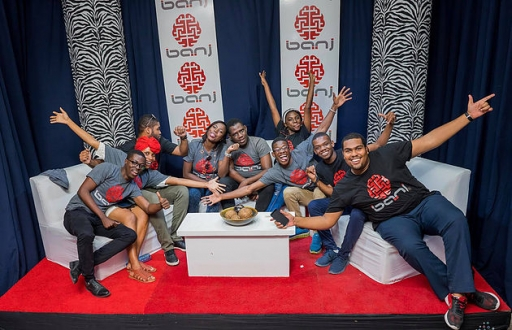 Group sitting on sofa poses for camera with exuberant facial expressions, all wearing Banj T-shirts, red carpet in front, colorful wall behind