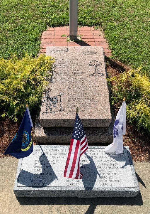 Flags hang next to a stone memorial engraved with names