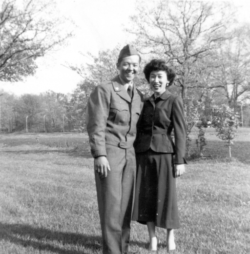 A black and white photo of a man in Army fatigues standing next to a woman in a suit jacket and skirt.