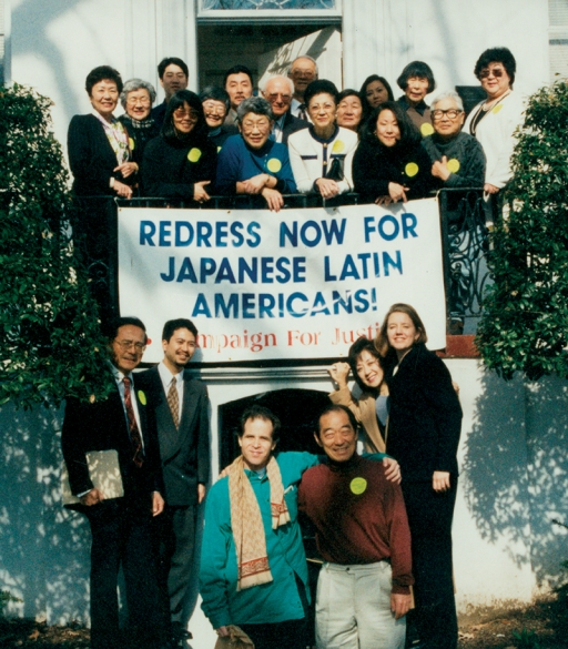 "A group of men and women stand on a balcony above a banner reading ""Redress now for Japanese Latin Americans."" Several people stand below the banner at ground level."