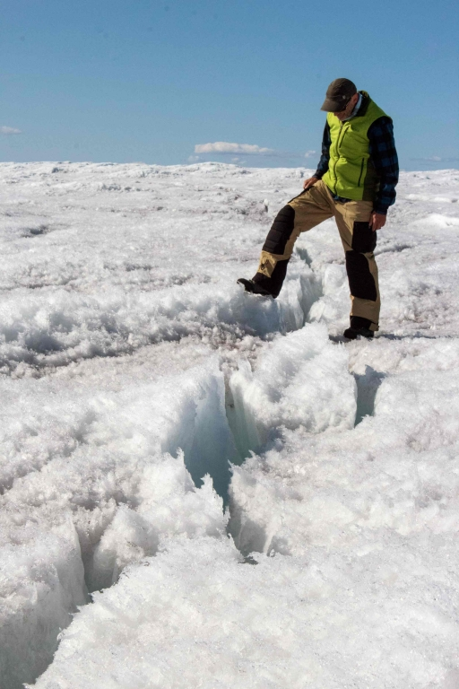 A man in a fluorescent vest steps over a large crack in the ice sheet.