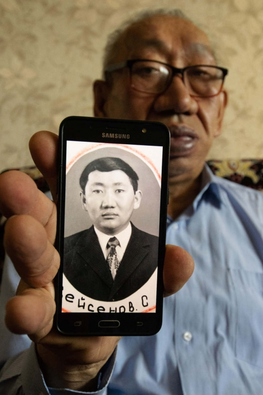 A man wearing glasses holds up a photo of his younger self on his mobile phone.