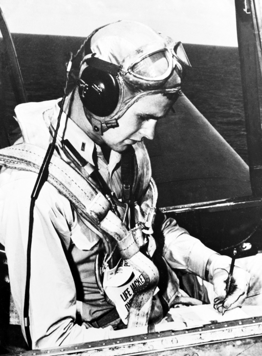 A young man in a pilot suit sits the cockpit of a WWII era Avenger plane