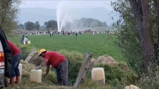 People are holding plastic gasoline containers. In the distance behind them, streams of gasoline spurts into the air out of a broken pipeline.
