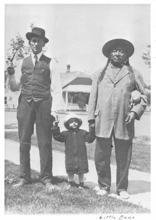Black and white image of one white man and one Indigenous man holding the hands of a child.