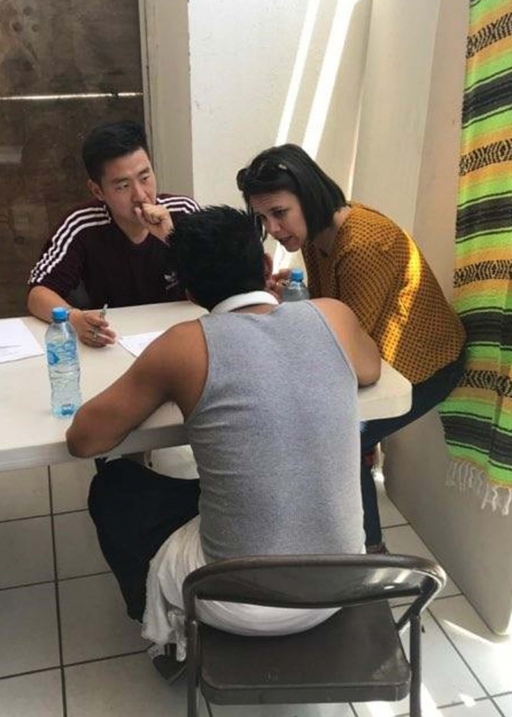 A student sits across from a man at a table. A woman leans at the table.