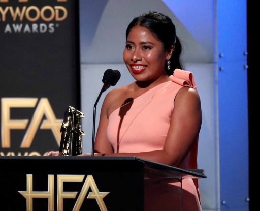 Yalitza Aparicio stands behind a podium holding the New Hollywood Award