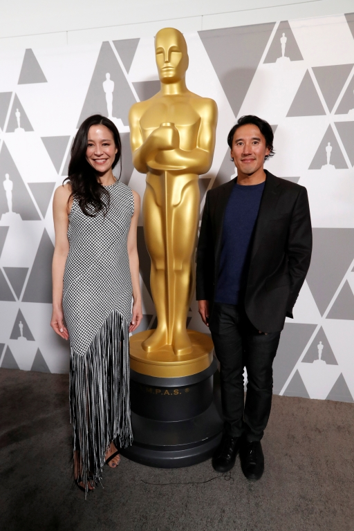 Jimmy Chin and Chai Vasarhalyi stand next to a human size Oscar statue
