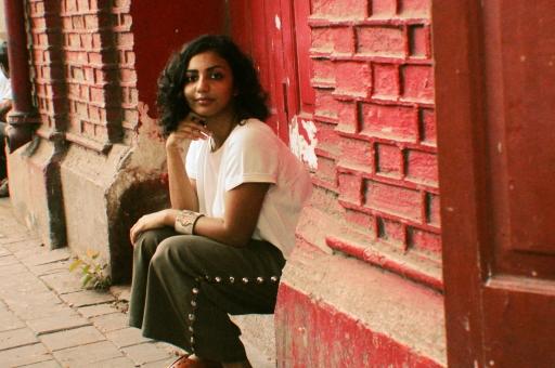 A woman sits on a ledge.
