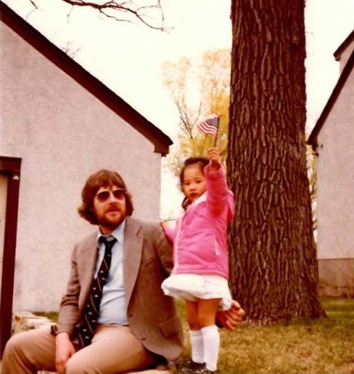 A white man and a small Korean girl in front of a house and tree. The girl waves an American flag.