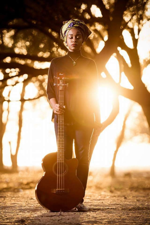 A woman poses with the sun behind her with a bass guitar