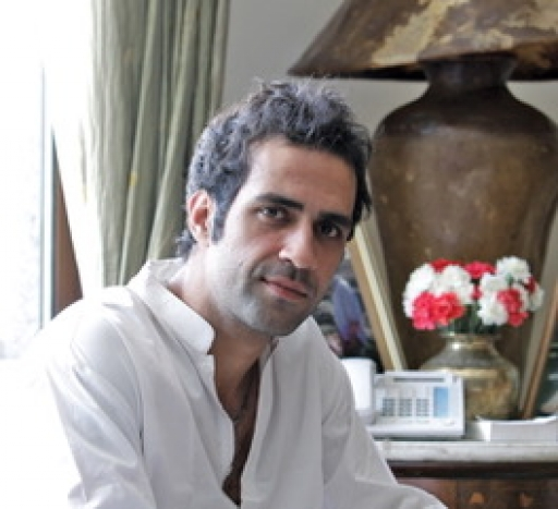 A portrait of author Aatish Taseer wearing a white shirt