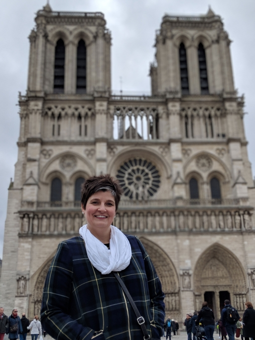 A woman poses for a photo in front of Notre-Dame's towers