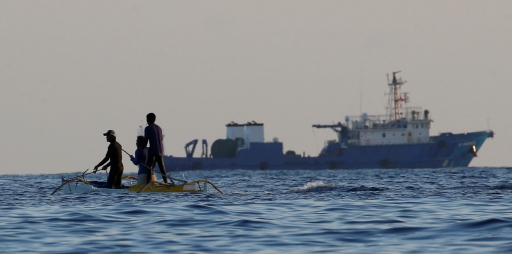 Two Filipino fishermen fish near large Chinese vessel in disputed waters