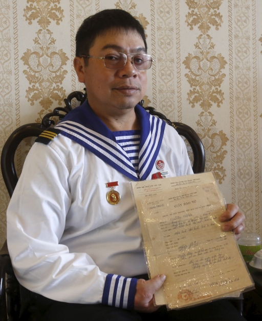 Man wears navy uniform and holds his own death certificate papers.