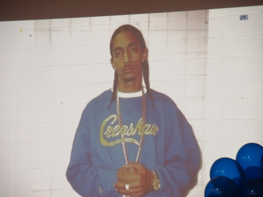 A photo of a black man with a shirt that says Crenshaw is projected on a wall