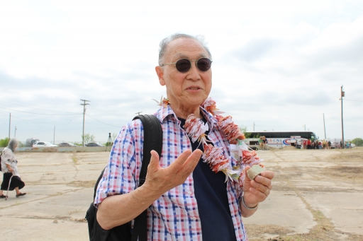 A man holds a piece of concrete as he talks to the camera