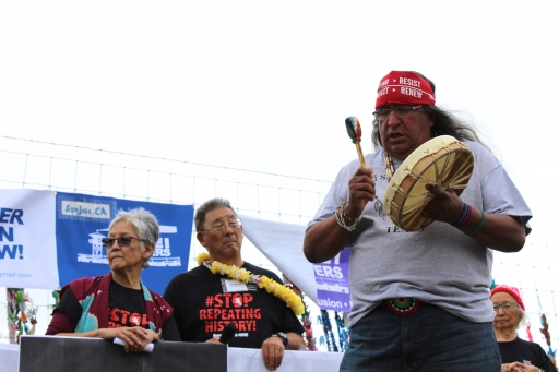 A woman and man stand behind a banner while another man plays a drum