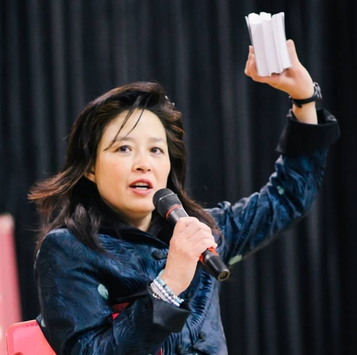 A woman in a jacket is holding a microphone and talking.