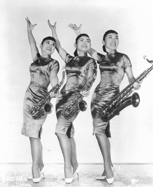 A black and white photo of three young Korean women posing with their hands up and holding saxophones.
