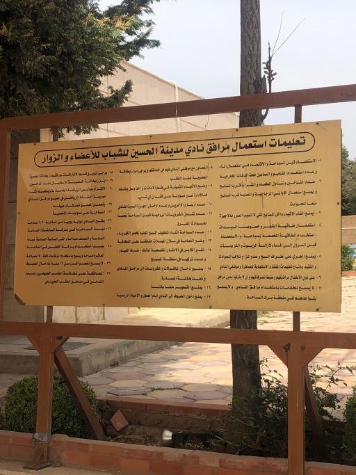 A sign is printed in Arabic outside a business