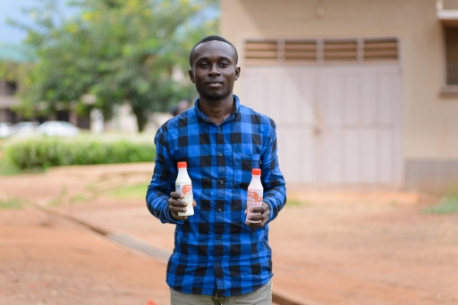 A young man holds his yogurt products