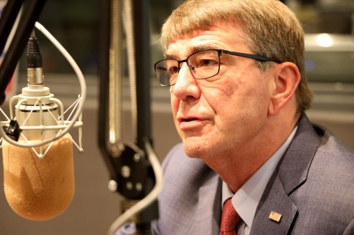 ash carter next to a microphone
